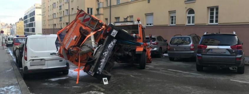 Umgestürztes Streufahrzeug beschädigt geparkte Pkw's
